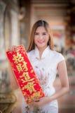 Aziatische vrouw in het Chinese 'sterke' couplet van de kledingsholding (Chinees Stock Fotografie