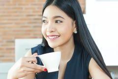 Aziatische Vrouw het drinken koffie met glimlach op haar gezicht royalty-vrije stock foto