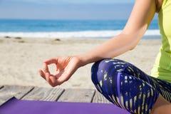 Aziatische vrouw het praktizeren yoga bij strand Royalty-vrije Stock Afbeelding