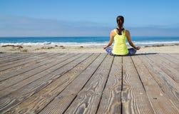 Aziatische vrouw het praktizeren yoga bij strand Royalty-vrije Stock Foto's