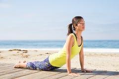 Aziatische vrouw het praktizeren yoga bij strand Stock Fotografie