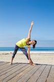 Aziatische vrouw het praktizeren yoga bij strand Stock Afbeelding