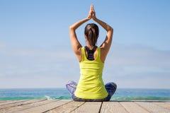 Aziatische vrouw het praktizeren yoga bij strand Royalty-vrije Stock Afbeeldingen