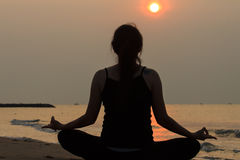 Aziatische vrouw het praktizeren yoga bij vredesoverzees in ochtend Stock Afbeeldingen