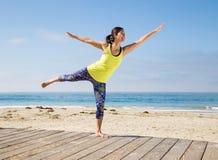 Aziatische vrouw het praktizeren yoga en hanving pret bij strand Stock Afbeelding
