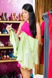 Aziatische vrouw het winkelen kleding in manieropslag Stock Foto's