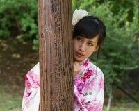 Aziatische vrouw in kimono achter houten pijler Stock Afbeeldingen