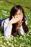 Aziatische vrouw met allergie in de lente die op gras liggen royalty-vrije stock afbeeldingen