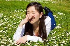 Aziatische vrouw met allergie in de lente die op gras liggen die bijna niezen stock fotografie