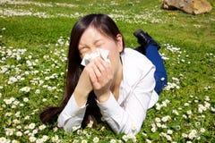 Aziatische vrouw met allergie in de lente die op gras liggen die met zakdoek niezen royalty-vrije stock foto