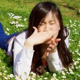 Aziatische vrouw met allergie in de lente die op grasclose-up liggen royalty-vrije stock foto's