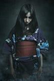 Aziatische vrouw met demonogen Royalty-vrije Stock Afbeeldingen