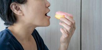 Aziatische vrouw met doughnut op houten achtergrond stock fotografie