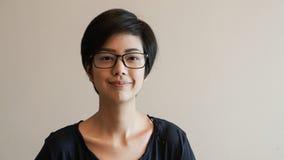 Aziatische vrouw met kort haar en glazen op kleurenachtergrond Royalty-vrije Stock Foto's