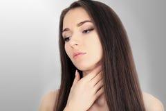 Aziatische vrouw met pijn in haar hals en schouder over grijze backgro Royalty-vrije Stock Afbeeldingen