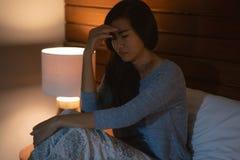 Aziatische vrouw met slaapwanorde in bed stock foto's