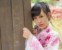 Aziatische vrouw naast deur die een kimono dragen stock fotografie