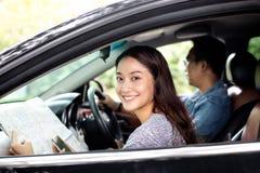 Aziatische vrouw smartphone en kaart gebruiken en mannen die auto op roa drijven Royalty-vrije Stock Foto