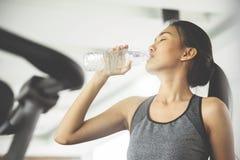 Aziatische vrouw in sportkledings drinkwater Royalty-vrije Stock Foto's