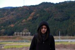 Aziatische vrouw in zwarte kleding en kap die zich openlucht bevinden royalty-vrije stock afbeeldingen