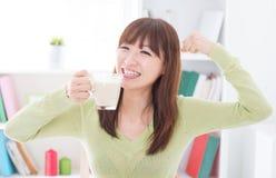 Aziatische vrouwelijke consumptiemelk en het tonen van sterk wapen Royalty-vrije Stock Afbeelding