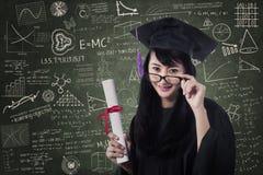 Aziatische vrouwelijke gediplomeerde in klasse met certificaat Stock Foto