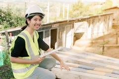 Aziatische vrouwelijke ingenieur Wearing een groene Zitting van het veiligheidsoverhemd in het bouwgebied stock afbeeldingen