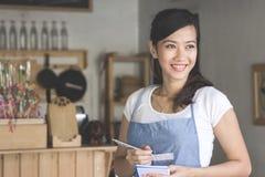 Aziatische vrouwelijke kelner in schort het schrijven orde Royalty-vrije Stock Foto's
