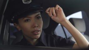 Aziatische vrouwelijke patrouillevrouw het aanpassen hoed, wachtende collega in ploegauto, politie stock video