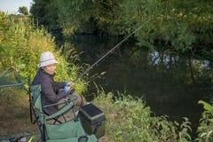 Aziatische Vrouwelijke Rivier die op een de Zomerdag vissen Stock Afbeeldingen