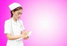 Aziatische vrouwelijke verpleegster die medisch rapport schrijft Royalty-vrije Stock Foto