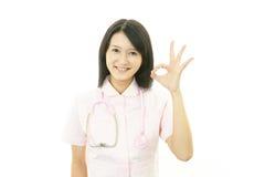 Aziatische vrouwelijke verpleegster met o.k. handteken Stock Afbeelding