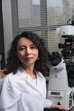 Aziatische vrouwelijke wetenschapperzitting bij microscoop Stock Afbeeldingen