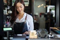 Aziatische vrouwen Barista die en koffiemachine in de teller van de koffiewinkel glimlachen met behulp van - Werkende vrouwen kle royalty-vrije stock afbeelding