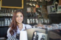 Aziatische vrouwen Barista die en koffiemachine in koffie s glimlachen met behulp van Stock Afbeelding