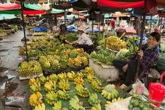 Aziatische vrouwen die banaanvruchten op de straatmarkt verkopen Stock Afbeeldingen