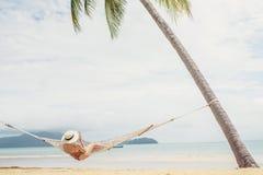 Aziatische vrouwen die in de vakantie van de hangmatzomer op strand ontspannen stock foto's