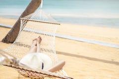 Aziatische vrouwen die in de vakantie van de hangmatzomer op strand ontspannen royalty-vrije stock afbeeldingen
