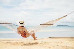 Aziatische vrouwen die in de vakantie van de hangmatzomer op strand ontspannen stock fotografie