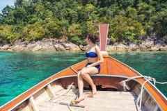 Aziatische vrouwen die in het tropische overzees van de de zomervakantie met lang-staartboot ontspannen in Thailand stock foto