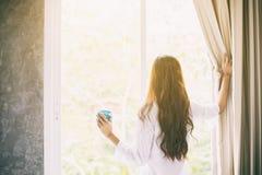 Aziatische vrouwen die koffie en ontwaken in haar bed drinken volledig reste royalty-vrije stock foto