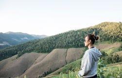 Aziatische vrouwen die mooi groen de gebieden en het graanlandbouwbedrijf van landschapsbergen in de ochtend kijken Stock Fotografie