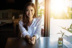 Aziatische vrouwen en het gelukkige Ontspannen die in een koffiewinkel na het werken in een succesvol bureau glimlachen royalty-vrije stock afbeeldingen