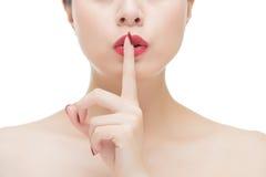 Aziatische vrouwen rode lippenstift en vinger die het teken van de stiltestilte tonen Stock Foto