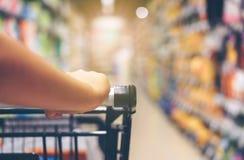 Aziatische vrouwen` s hand met supermarkt, karretje en vele objecten Th stock afbeelding