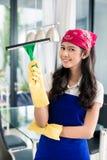 Aziatische vrouwen schoonmakende vensters in haar huis Royalty-vrije Stock Foto's