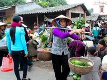 Aziatische vrouwen verkopende groenten bij de markt Royalty-vrije Stock Afbeeldingen