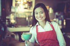 Aziatische vrouwenbarista die met een kop van koffie in haar hand glimlachen Royalty-vrije Stock Foto