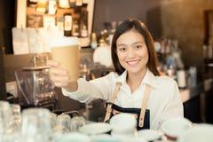 Aziatische vrouwenbarista die met een kop van koffie in haar hand glimlachen Stock Foto's