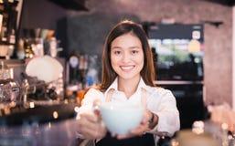 Aziatische vrouwenbarista die met een kop van koffie in haar hand glimlachen Stock Afbeeldingen